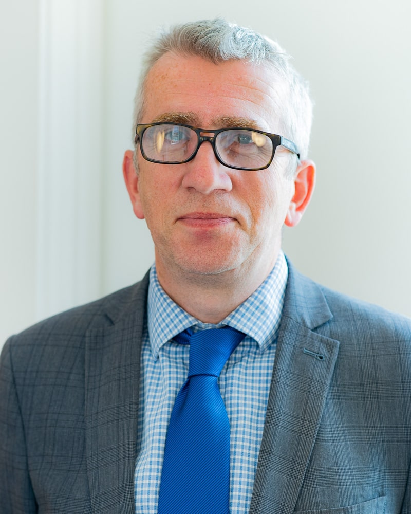 Professional headshot of a man in glasses in natural light taken in a corporate office
