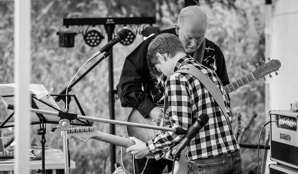 A man and a boy sharing their musical talents at an outdoor musical event